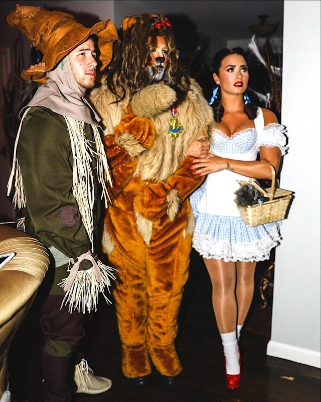 <p>Tour mates Jonas and Lovato were part of a <i>Wizard of Oz</i> group costume at a Beverly Hills bash. (Photo: AKM-GSI) </p>