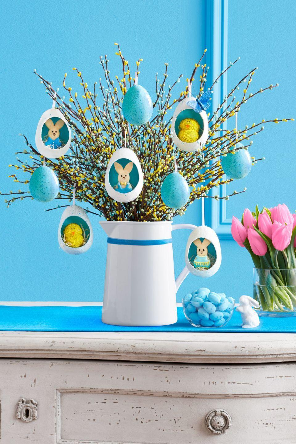 """<p>Use a craft knife to cut a 2"""" x 2"""" oval into 4"""" eggs. Apply one to two coats of paint to the 4"""" and 2"""" eggs; let dry. Stuff 4"""" eggs with tissue paper, then place all eggs inside cardboard box. In small bowl, mix a few drops of water with a dollop of paint, then dip the toothbrush bristles in and use your thumb to fleck the paint onto the eggs to create speckles. Once dry, repeat for the reverse side of the eggs. Place floral foam inside the flower bucket and arrange sprays inside. Use brown floral tape to attach two sprays together to create height as needed. Hot-glue a small loop of ribbon to the top of the eggs and hang from spray branches. Arrange Easter grass inside 4"""" eggs, then add cookies.</p><p><strong><a class=""""link rapid-noclick-resp"""" href=""""https://www.amazon.com/X-Acto-XZ3601-X-ACTO-Knife-Safety/dp/B005KRSWM6/?tag=syn-yahoo-20&ascsubtag=%5Bartid%7C10070.g.1751%5Bsrc%7Cyahoo-us"""" rel=""""nofollow noopener"""" target=""""_blank"""" data-ylk=""""slk:SHOP CRAFT KNIVES"""">SHOP CRAFT KNIVES</a></strong></p>"""