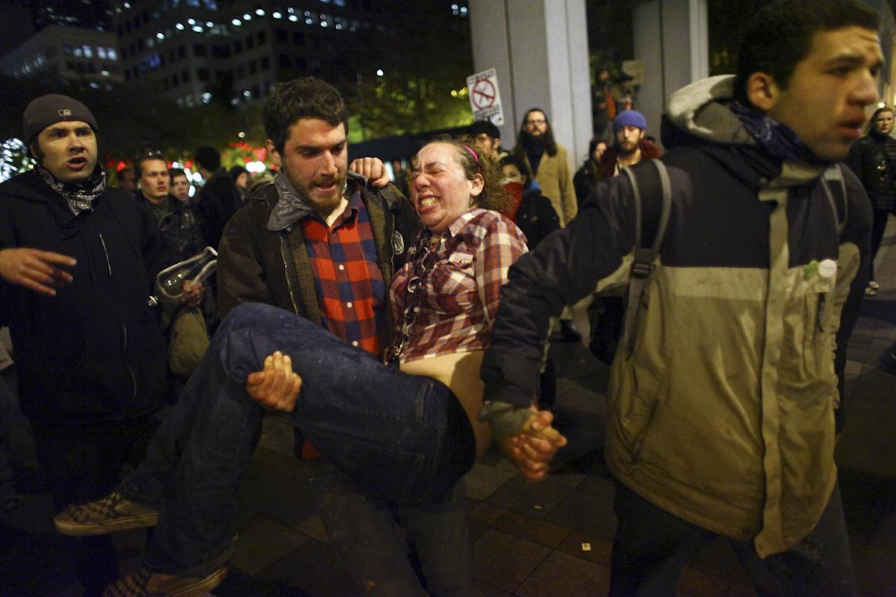 A woman who gave her name as Jennifer and said she was two months pregnant is rushed to an ambulance after being hit with pepper spray at an Occupy Seattle protest on Tuesday, Nov. 15, 2011 at Westlake Park in Seattle. Protesters gathered in the intersection of 5th Avenue and Pine Street after marching from their camp at Seattle Central Community College in support of Occupy Wall Street. Many refused to move from the intersection after being ordered by police. Police then began spraying pepper spray into the gathered crowd hitting dozens of people. (AP Photo/seattlepi.com, Joshua Trujillo) MAGS OUT; NO SALES; SEATTLE TIMES OUT; TV OUT; MANDATORY CREDIT