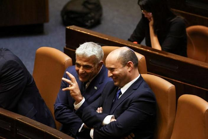 Prime Minister Naftali Bennett chats with Foreign Minister Yair Lapid, following the vote for the new coalition at the Knesset, Israel's parliament, in Jerusalem