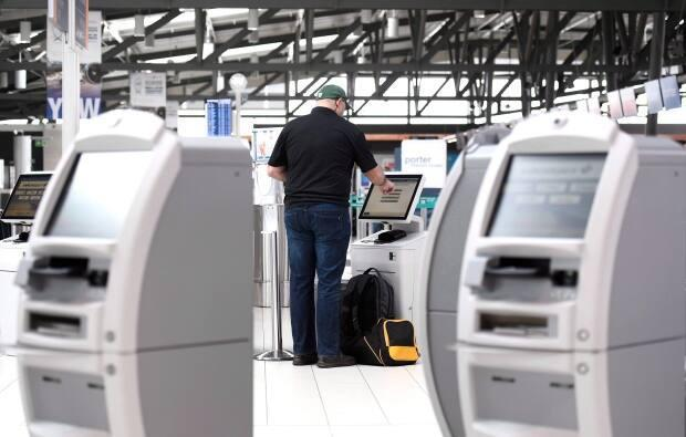 Once international travel resumes, self-serve check in terminals like these at Ottawa International Airport will become part of a more hands-free travel experience. (The Canadian Press/Justin Tang - image credit)