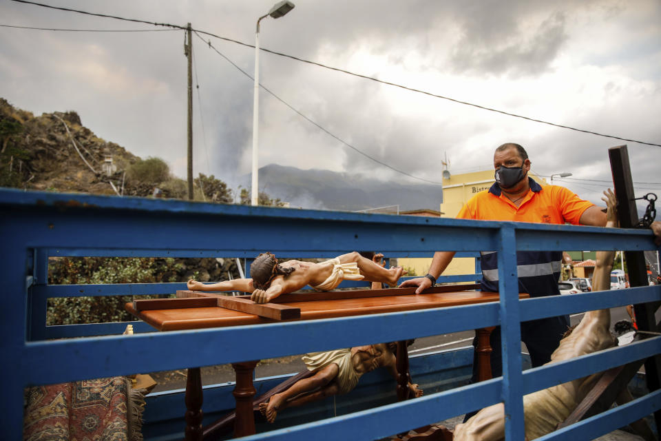 Crucifixes of Jesus Christ lie in the back of a truck after being saved from the San Pio X church in El Paso on the island of La Palma in the Canaries, Spain, Monday, Sept. 20, 2021. Giant rivers of lava are tumbling slowly but relentlessly toward the sea after a volcano, seen in backround, erupted on a Spanish island off northwest Africa. The lava is destroying everything in its path but prompt evacuations helped avoid casualties after Sunday's eruption.(Kike Rincon, Europa Press via AP)