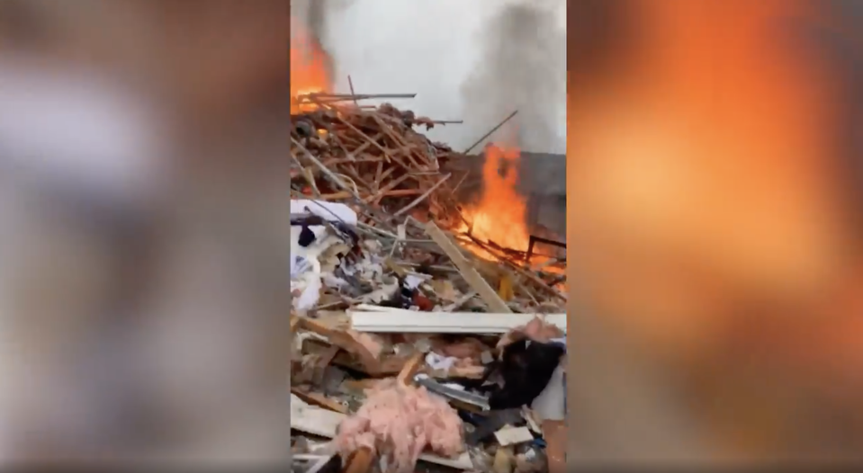This picture shows a pile of debris and flames coming from a home which exploded in Christchurch.