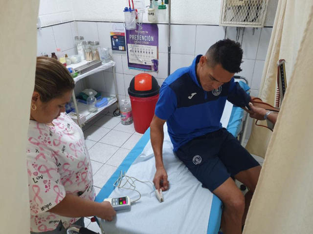 This photo, courtesy of Club Deportivo Motagua, shows Roberto Moreira, a Pagauayan player with the Motagua soccer club, at a clinic as he is attend after his team's bus was attacked by fans of a rival team before a game in Tegucigalpa, Honduras, late Saturday, Aug. 17, 2019. The fight reportedly began when Olimpia fans attacked with stones and vandalized the bus carrying Motagua players to the stadium on Saturday. (Club Deportivo Motagua via AP)