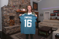 Clemson quarterback Trevor Lawrence holds up a jersey after being selected by the Jacksonville Jaguars with the first pick in the NFL football draft, Thursday, April 29, 2021, in Seneca, S.C. (Logan Bowles/NFL via AP)