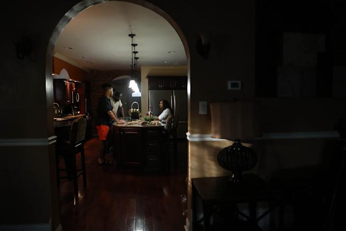 Omar Chatt talks with his mother, Rosita González, as his uncle cooks dinner for the family on June 15.