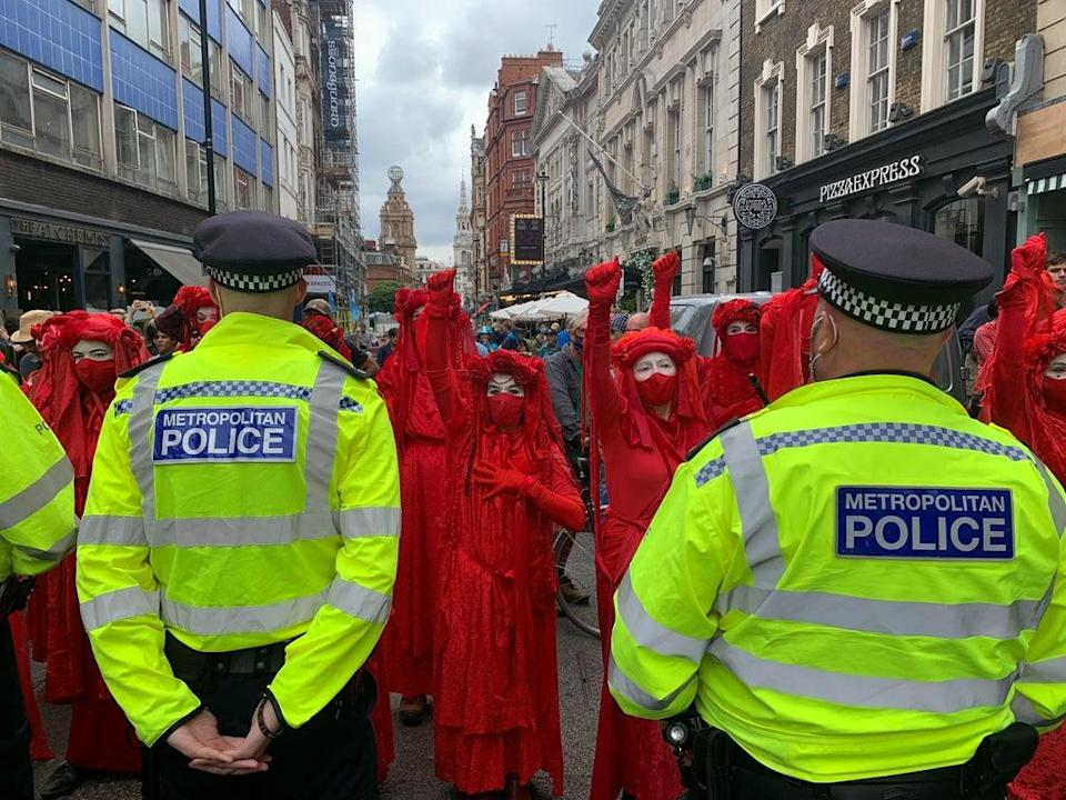 XR's infamous red-robed protesters stand in front of one of the six human barriers formed by Met Police officers (The Independent)