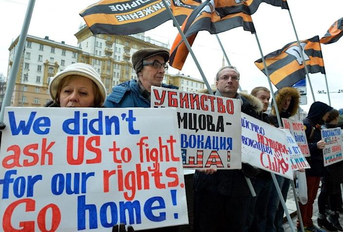 People hold placards during a protest against US international policy in front of the US embassy (background) in central Moscow on March 7, 2015 (AFP Photo/Yuri Kadobnov)