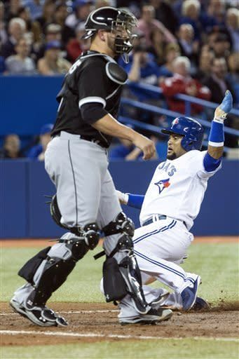 Toronto Blue Jays' Emilio Bonifacio, right, scores at home plate in front of Chicago White Sox catcher Tyler Flowers after an error by first baseman Adam Dunn during the fifth inning of a baseball game in Toronto on Thursday, April 18, 2013. (AP Photo/The Canadian Press, Chris Young)