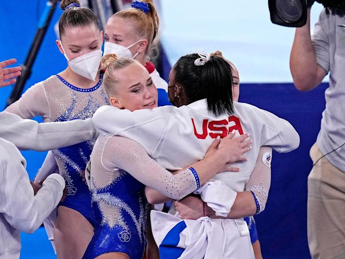 Simone Biles hugs members of the Russian Olympic Committee after their gold-medal finish.