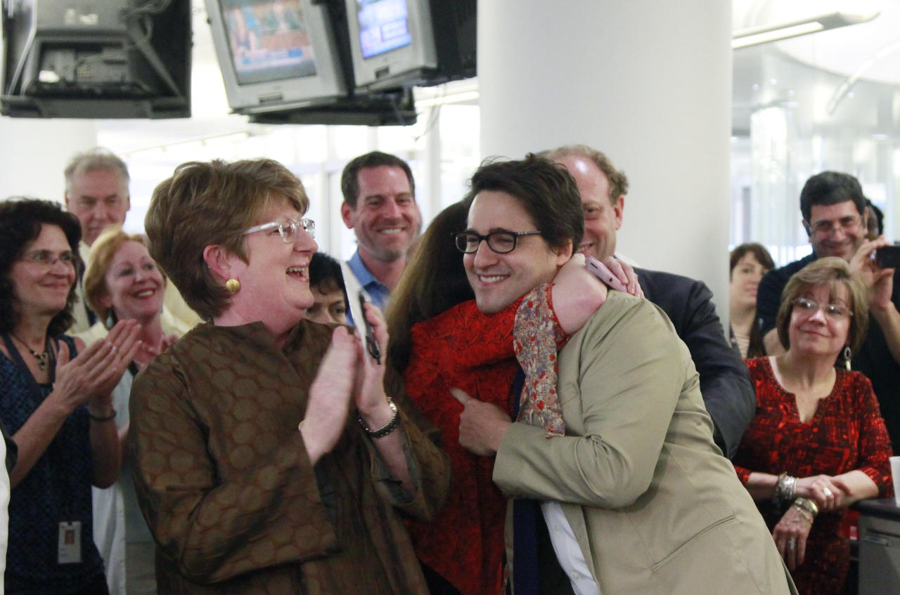 Executive Associated Press Editor Kathleen Carroll, left, applauds as Associated Press reporter Adam Goldman, center, is hugged after winning the Pulitzer Prize for Investigative Reporting with three colleagues, Monday, April 16, 2012 in New York. They revealed a secret New York Police Department program that spied on Muslim neighborhoods. (AP Photo/Mark Lennihan)