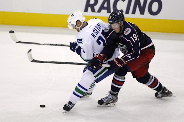 Columbus' Ryan Johansen (19) collides with Vancouver's Henrik Sedin, of Sweden, during the third period of an NHL hockey game Sunday, Oct. 20, 2013, in Columbus, Ohio. (AP Photo/Mike Munden)
