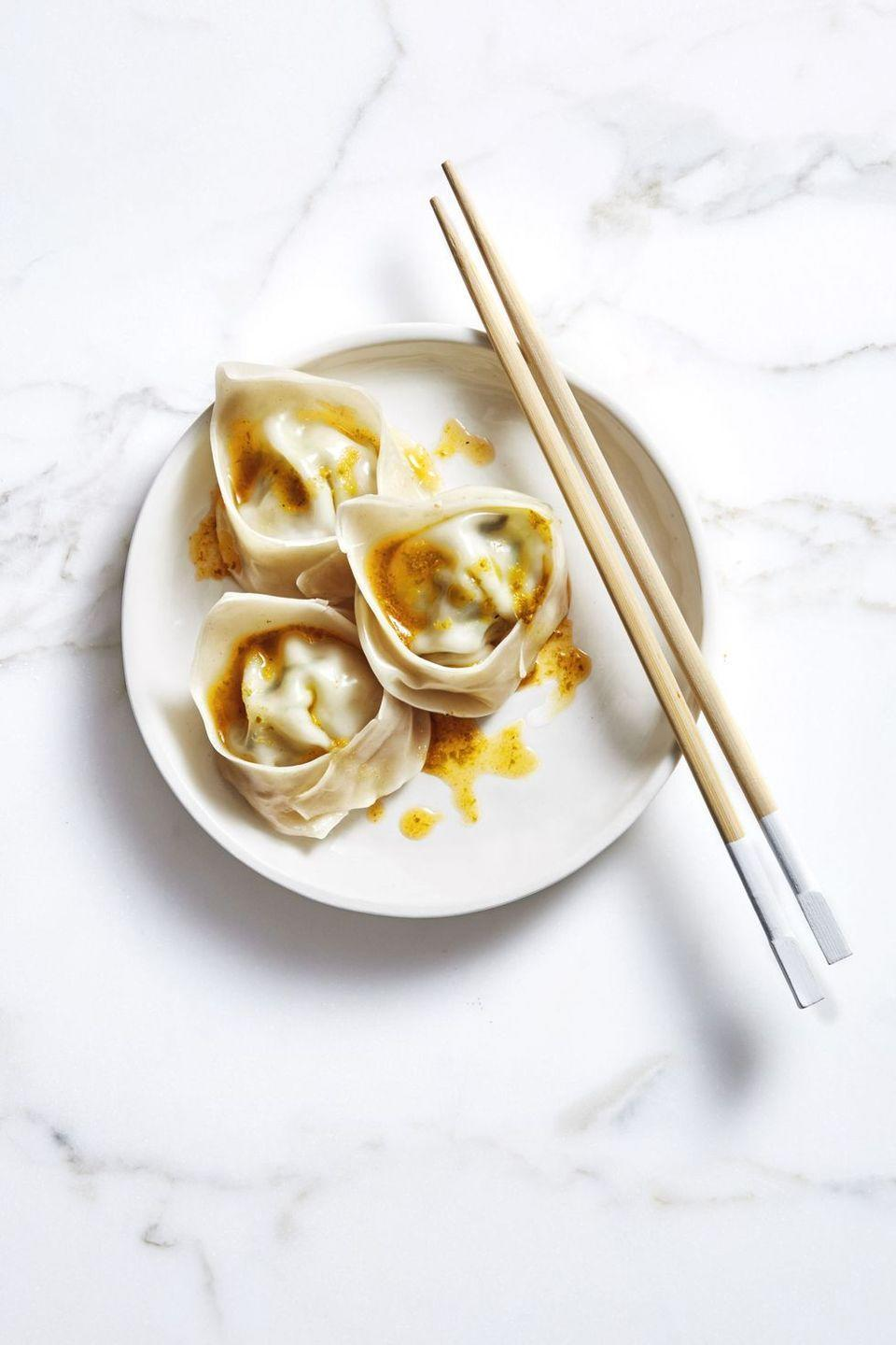 """<p>These delicious dumplings are easier to make than you think — and absolutely incredible when served with a spicy chili oil.</p><p><em><a href=""""https://www.goodhousekeeping.com/food-recipes/a47683/gingery-pork-and-chive-wontons-recipe/"""" rel=""""nofollow noopener"""" target=""""_blank"""" data-ylk=""""slk:Get the recipe for Gingery Pork and Chive Wontons »"""" class=""""link rapid-noclick-resp"""">Get the recipe for Gingery Pork and Chive Wontons »</a></em></p>"""