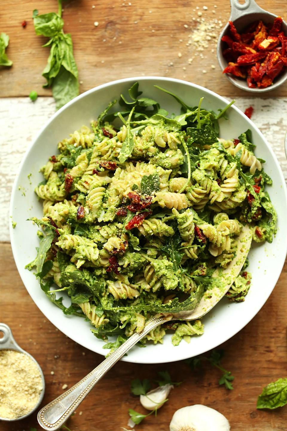 Plate of freshly made pea pesto pasta with bits of sliced sundried tomatoes.