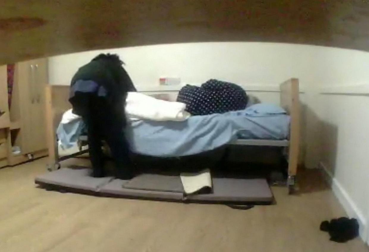 """This disturbing footage shows the moment care home staff dragged a quivering and distressed disabled pensioner across her room - leaving her in a urine-stained bed.  See SWNS story SWLEcare.  Michael Lanera captured the images on a camera he fitted in his 85-year-old dementia-ridden mother's room after he suspected she was being mistreated.  The shocking video shows nurse Mamello Herring and care worker Maria Jackson dragging Angelina Lanera from the toilet back to her bed with her knickers around her ankles.  Mrs Lanera can be heard screaming and crying in distress, but the workers continue to manhandle her using a banned """"drag lift"""" technique.  The banned technique involves someone putting a hand or arm under the person's armpit and can result in injuries to those involved.  They then left her in the urine-stained bed and clothes, Bradford Crown Court heard on Friday (22 Jan).  Mr Lanera set up the camera after he suspected his mother wasn't being properly looked after at a care home in Halifax, West Yorks."""