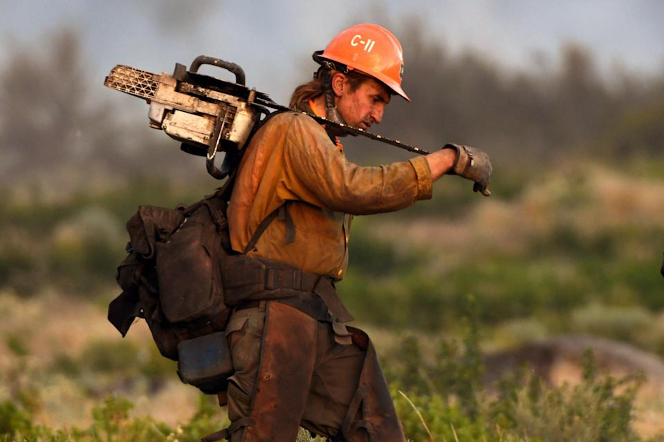 A member of the U.S. Forest Service's Trinity Hotshots firefighting crew carries a chain saw while hiking out of the burn zone Monday, June 28, 2021, at the Lava Fire north of Weed, Calif. (Scott Stoddard/Grants Pass Daily Courier via AP))
