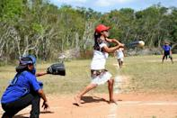 A player for the Little Devils of Hondzonot swings the bat during a softball game against the Piste Warriors in rural southeast Mexico
