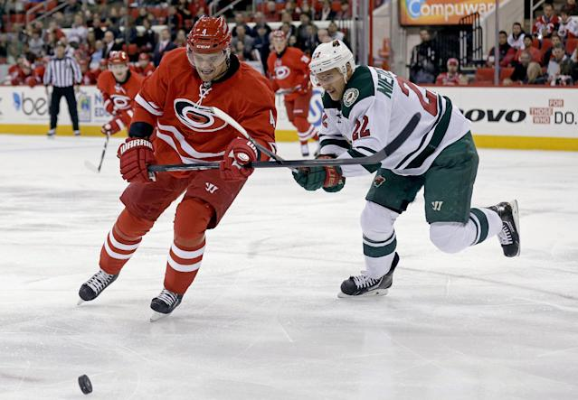 Carolina Hurricanes' Andrej Sekera (4), of Slovakia, and Minnesota Wild's Nino Niederreiter (22), of Switzerland, chase the puck during the first period of an NHL hockey game in Raleigh, N.C., Saturday, Nov. 9, 2013. (AP Photo/Gerry Broome)