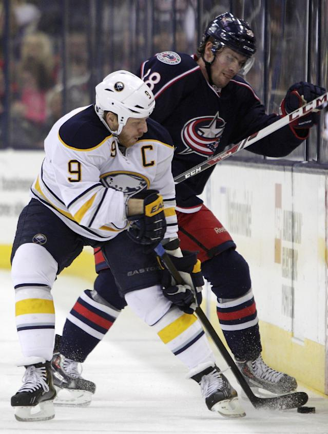 Buffalo Sabres' Steve Ott, left, and Columbus Blue Jackets' Boone Jenner fight for a loose puck during the first period of an NHL hockey game, Saturday, Jan. 25, 2014, in Columbus, Ohio. (AP Photo/Jay LaPrete)