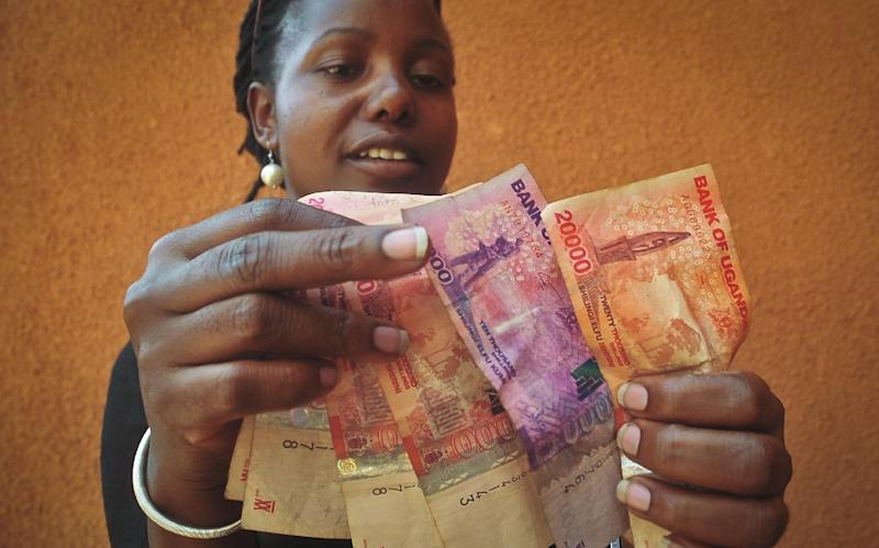 A Ugandan businesswoman who sells cereals counts Ugandan Shilling banknotes in Kampala, Uganda Thursday, Feb. 27, 2014. The value of the Ugandan shilling has fallen in recent days, after Uganda's government was hit with substantial aid cuts following the president enacting a severe anti-gay measure over which some Western governments had warned of consequences. (AP Photo/Stephen Wandera)