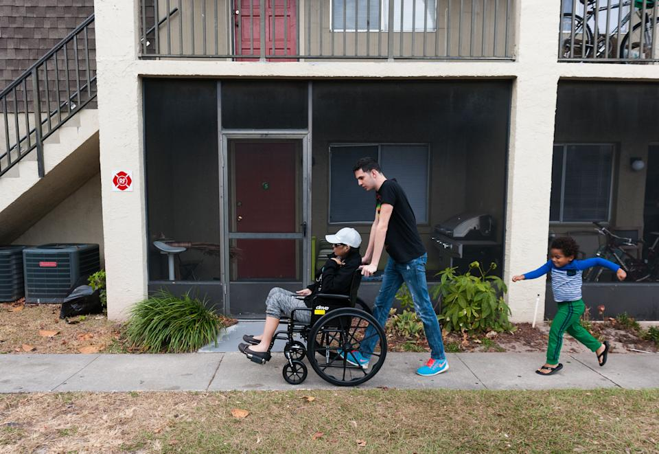 Jan Miguel pushes his mother, Mariluz, in a wheelchair on their way to get a ride to a doctor appointment. Jan Miguel's cousin Emiliano follows closely. (Photo: Chris McGonigal/HuffPost)