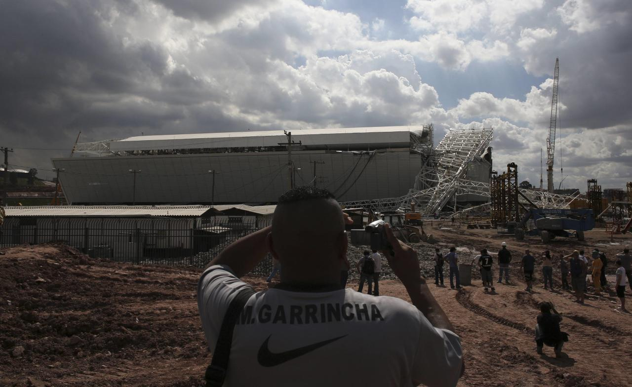 "A man records the crane that collapsed on the site of the Arena Sao Paulo stadium, known as ""Itaquerao"", which will host the opening soccer match of the 2014 World Cup, in Sao Paulo November 27, 2013. A crane collapsed on Wednesday at the construction site of a future World Cup soccer stadium in Sao Paulo, Brazil, killing at least three people and causing damage to the structure, local media said. REUTERS/Nacho Doce (BRAZIL - Tags: SPORT SOCCER WORLD CUP)"