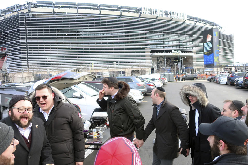 Men dance in a circle to celebrate after reading the Talmud in front of MetLife Stadium Wednesday, Jan. 1, 2020, in East Rutherford, N.J., at an event called Siyum HaShas, that celebrates the completion of the reading of the Babylonian Talmud, a process that takes 7 1/2 years The large gathering of Jews drew a significant security presence after recent anti-Semitic attacks in the New York City area. (AP Photo/Ted Shaffrey)