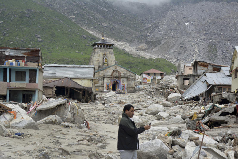 In this Thursday June 20, 2013, photo, a pilgrim takes pictures of an area devastated following heavy monsoon rains at Kedarnath, in the northern Indian state of Uttrakhand. A joint army and air force operation are trying to evacuate thousands of people stranded in the upper reaches of the state of Uttrakhand where days of rain had earlier washed out houses, temples, hotels and vehicles leading to deaths of over a hundred people amid fears that the death toll may rise much higher. (AP Photo)