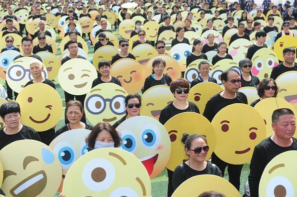 People dress as emoji faces to set an Guinness World Record on a school playground on May 27, 2018 in Fuyang, Anhui Province of China. Guinness World Record of most people dressed up as emoji faces was achieved by 932 participants on Sunday in Fuyang. (Photo by VCG/VCG via Getty Images)
