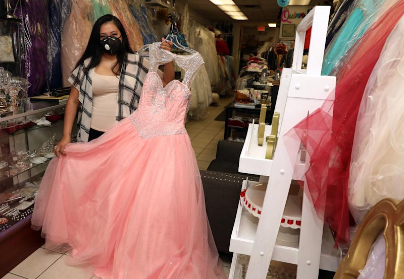 Jessica Larios, owner of Bella's Events, which specializes in rentals and sales of anything party related, holds a Quinceanera dress at the shop in Yonkers May 28, 2020. The Acceleration Project, a Scarsdale nonprofit consulting firm that is helping small businesses survive during the pandemic helped Larios navigate the loans process and adapt her business by moving it online.