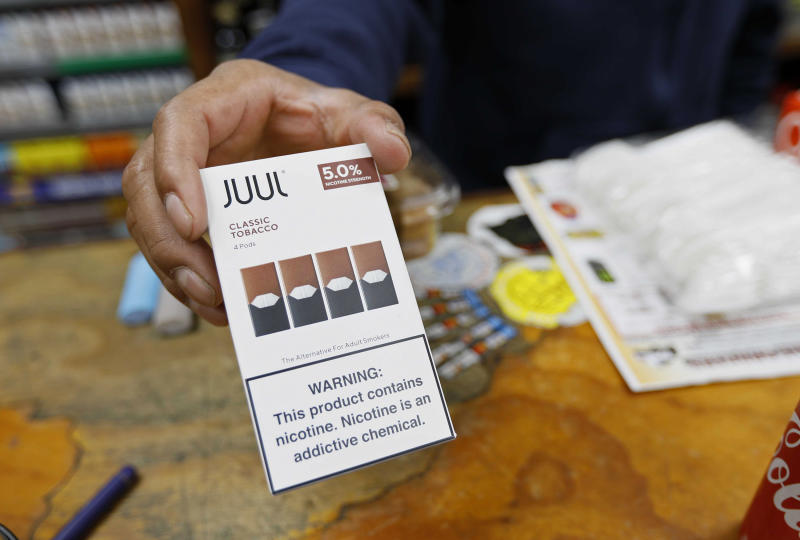 In this Monday, June 17, 2019, photo, a cashier displays a packet of tobacco-flavored Juul pods at a store in San Francisco. San Francisco supervisors are considering whether to move the city toward becoming the first in the United States to ban all sales of electronic cigarettes in an effort to crack down on youth vaping. The plan would ban the sale and distribution of e-cigarettes, as well as prohibit e-cigarette manufacturing on city property. Business owners say it would hurt their businesses. (AP Photo/Samantha Maldonado)