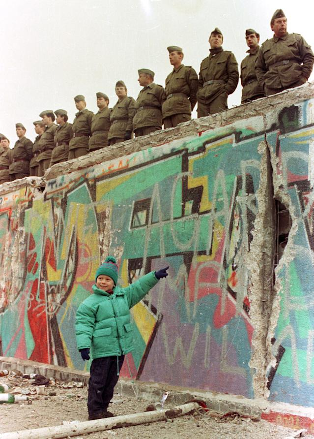 A young West German girl smiles at her father as she points to a large hole in the Berlin Wall on Nov. 11, 1989. (Photo: Reuters)