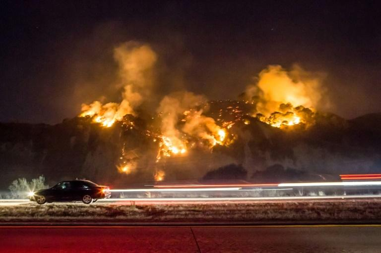 A car drives past as the Thomas Fire burns a hillside south of Casitas Springs, California