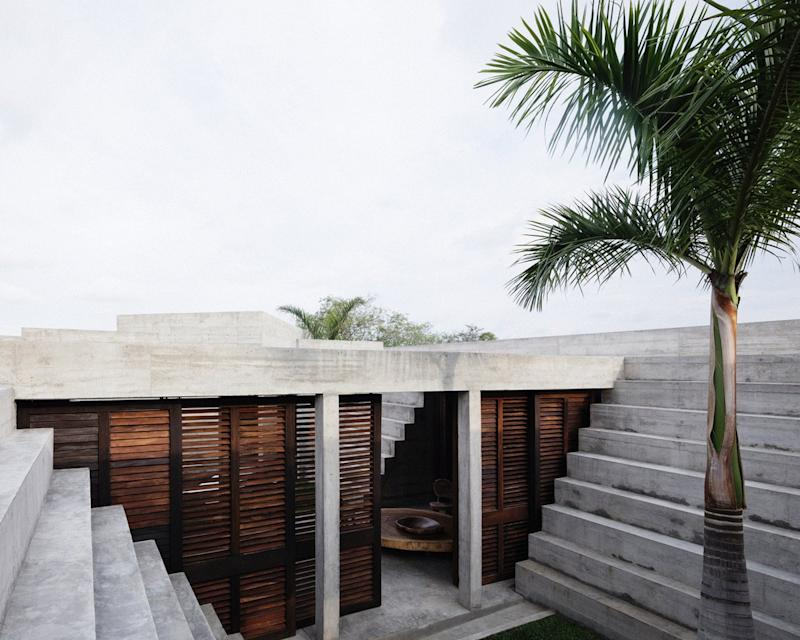 Timber shutters and wide open doorways keep the otherwise-cold feeling Zicatela House connected to nature at all times.