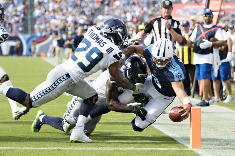 The Seahawks' Earl Thomas, left, and Kam Chancellor tackle Titans quarterback Marcus Mariota as Mariota reaches the ball toward the goal line during a 2017 game.