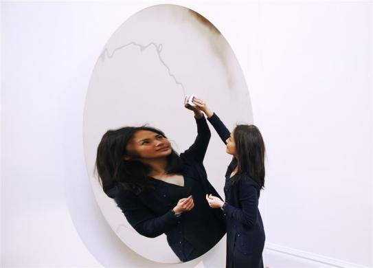 A Sotheby's employee poses with Anish Kapoor's Untitled artwork at Sotheby's auction house in London February 1, 2012.