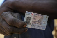 """Haitian migrant Carlo Richard shows his expired Chilean identity card, which was good for six months then rejected for renewal, at home in a camp named """"Bosque Hermoso,"""" or Beautiful Forest in Lampa, Chile, Friday, Oct. 1, 2021. The auto mechanic who has resided in Chile since 2017 is one of thousands who live in fear of being expelled. (AP Photo/Esteban Felix)"""