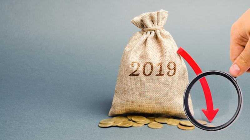 Bag with 2019 printed on it, gold coins beside it, and a red arrow pointing down extending from it with a hand holding a magnifying glass over the red arrow