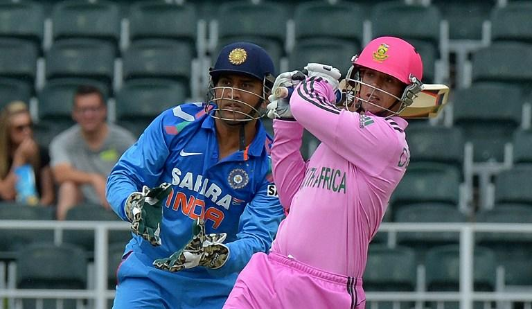 South Africa's batsman Quinton de Kock (R) plays a shot as India's captain and wicketkeeper Mahendra Singh Dhon looks on during the first One-Day International (ODI) match between South Africa and India in Johannesburg at the Wanderers Stadium on December 5, 2013.  AFP PHOTO / ALEXANDER JOE