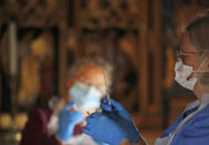 Health workers prepare the Pfizer-BioNTech vaccine inside Salisbury Cathedral in Salisbury, England, Wednesday, Jan. 20, 2021. Salisbury Cathedral opened its doors for the second time as a venue for the Sarum South Primary Care Network COVID-19 Local Vaccination Service. (AP Photo/Frank Augstein)