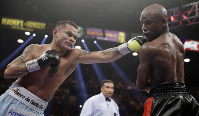 Marcos Maidana, left, from Argentina, throws a left at the head of Floyd Mayweather Jr. in their WBC-WBA welterweight title boxing fight Saturday, May 3, 2014, in Las Vegas. (AP Photo/Isaac Brekken)