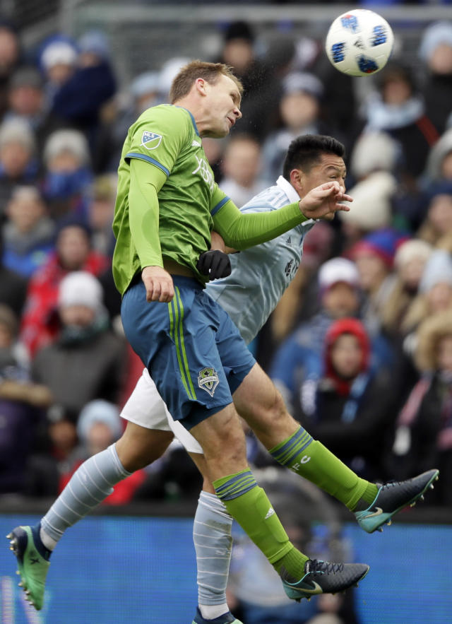Seattle Sounders defender Chad Marshall, front, heads the ball against Sporting Kansas City midfielder Roger Espinoza, back, during the first half of an MLS soccer match in Kansas City, Kan., Sunday, April 15, 2018. (AP Photo/Orlin Wagner)