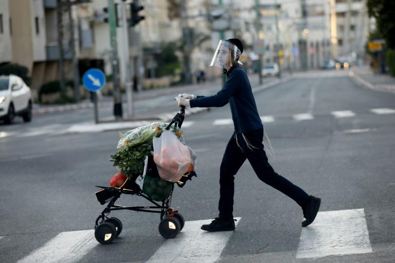 An ultra-Orthodox Jewish youth wearing a protective plastic mask crosses a street with his shopping in the Israeli city of Bnei Brak near Tel Aviv