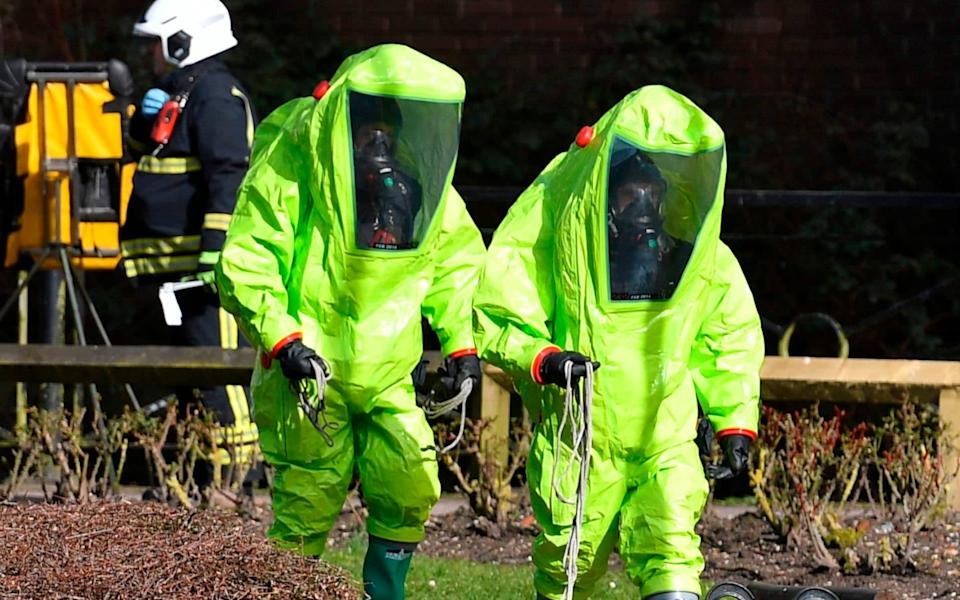 FILES) In this file photo taken on March 08, 2018 members of the fire brigade in green biohazard encapsulated suits work to re-attach the tent at the scene of a nerve agent attack at The Maltings shopping centre in Salisbury, southern England. - The English town of Salisbury is officially decontaminated, the government said Friday, almost a year after it was the scene of a nerve agent attack on Russian ex-spy Sergei Skripal. - Ben STANSALL/AFP/Getty Images