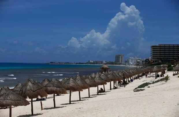 Tourists relax on a beach in Cancun, Mexico, last month. Several airlines in Canad with routes south say the fall and winter seasons are looking promising. (Marco Ugarte/The Associated Press - image credit)