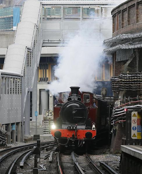 Metropolitan 1, a restored steam train built in 1898, passes through Farringdon Tube station on it's journey between Olympia Tube station in the west to Moorgate station in the City of London, Sunday, Jan. 13, 2013, as part of the celebrations for the 150th anniversary of the London Underground Tube system. The first stretch of the world-famous network opened to the public on Jan. 10, 1863. (AP Photo/Alastair Grant)