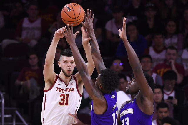 Southern California forward Nick Rakocevic, left, passes the ball while under pressure from Washington guard Nahziah Carter, center, and forward Isaiah Stewart during the first half of an NCAA college basketball game Thursday, Feb. 13, 2020, in Los Angeles. (AP Photo/Mark J. Terrill)