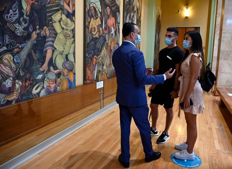 A tour guide speaks to visitors at the Fine Arts Palace in Mexico City, on September 2, 2020, amid the new coronavirus pandemic. - The novel coronavirus has killed at least 857,824 people worldwide since the outbreak last December, according to a tally from official sources compiled by AFP, with Mexico being one of the hardest-hit countries with 65,241 deaths from 606,036 cases. (Photo by ALFREDO ESTRELLA / AFP) / RESTRICTED TO EDITORIAL USE - TO ILLUSTRATE THE EVENT AS SPECIFIED IN THE CAPTION (Photo by ALFREDO ESTRELLA/AFP via Getty Images)