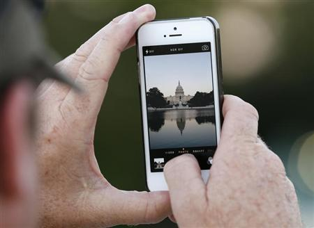 A man takes a photo of the U.S. Capitol, on the eve of a potential federal government shutdown, in Washington