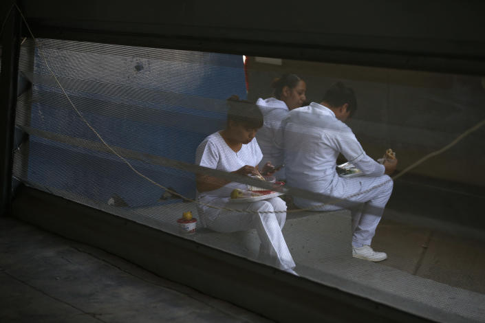 Medical workers take a lunch break outside the vaccination site, as the city health department conducts a mass coronavirus vaccination campaign for Mexicans over age 60, at Palacio de los Deportes, in Mexico City, Wednesday, Feb. 24, 2021. (AP Photo/Rebecca Blackwell)